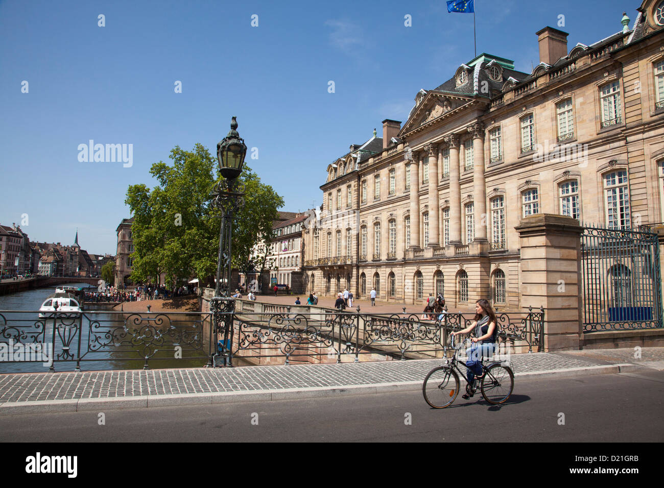 Woman riding a bike across bridge over Ill river, Strasbourg, Alsace, France, Europe - Stock Image