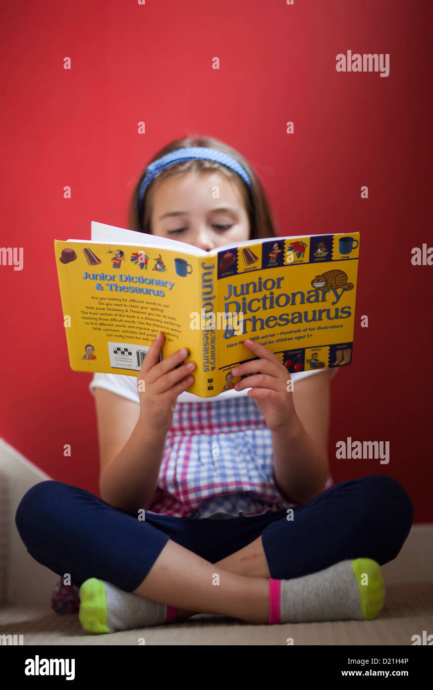 A young girl reading a junior dictionary and thesaurus Stock