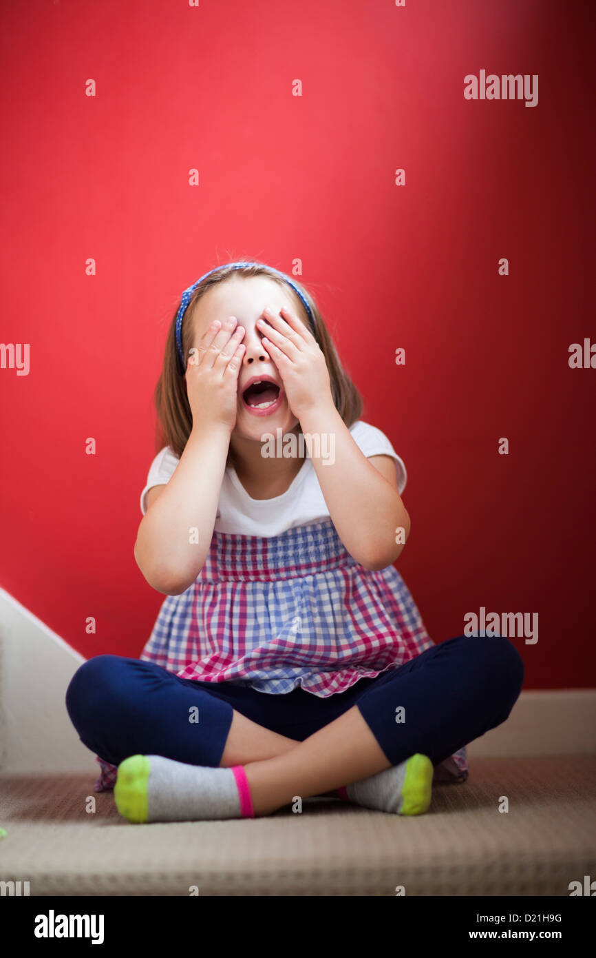 A young girl covering her eyes and counting during a game of hide and seek. - Stock Image