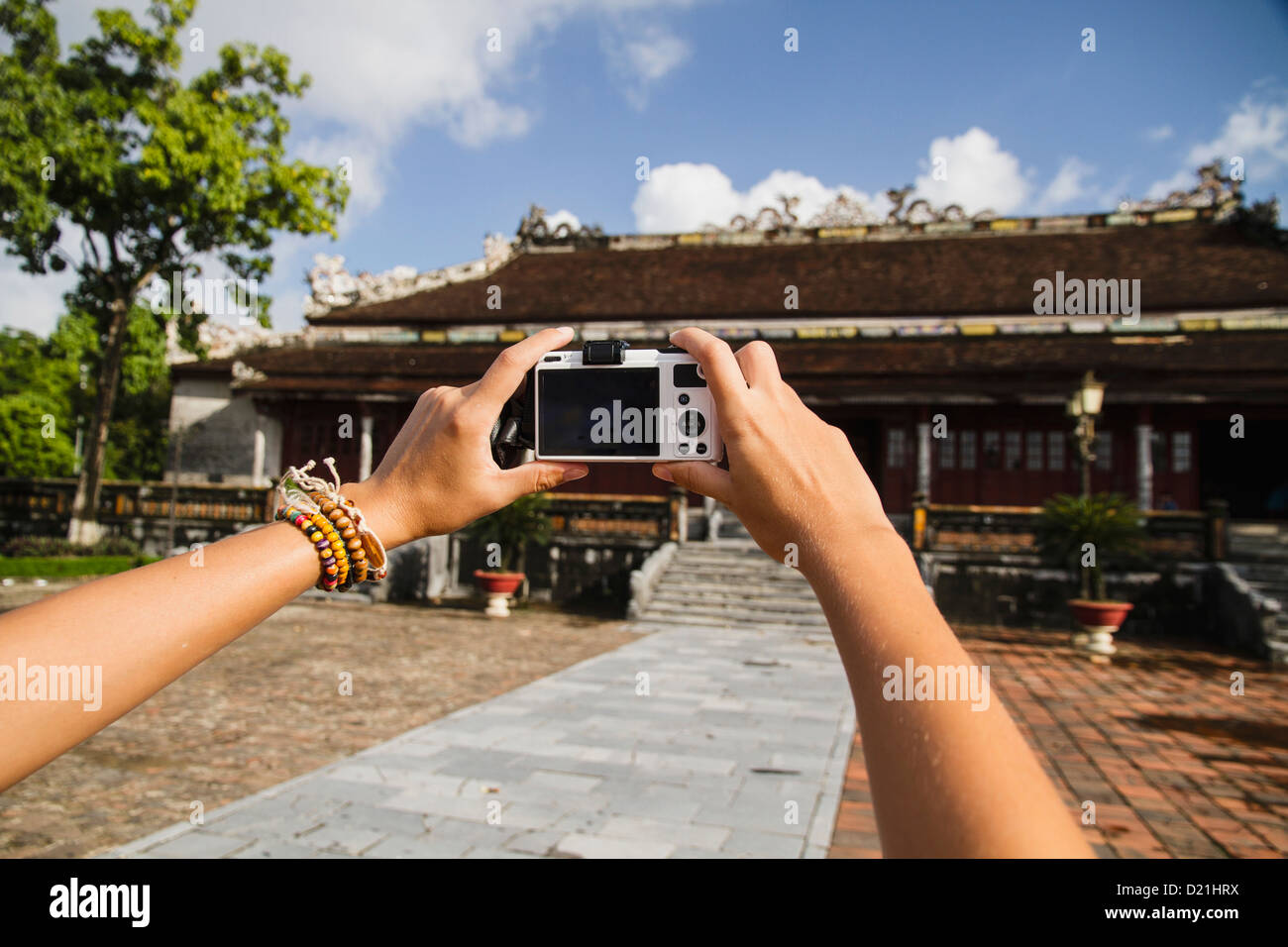 Vietnam, Hue, Young woman taking photograph of Can Chanh palace - Stock Image