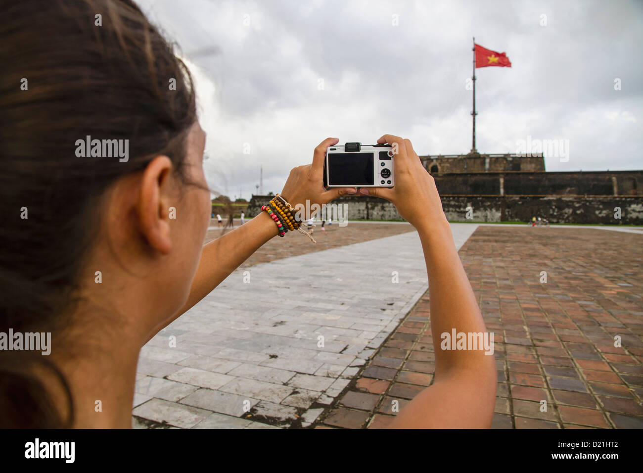 Vietnam, Hue, Young woman taking photograph of Hue Citadel - Stock Image