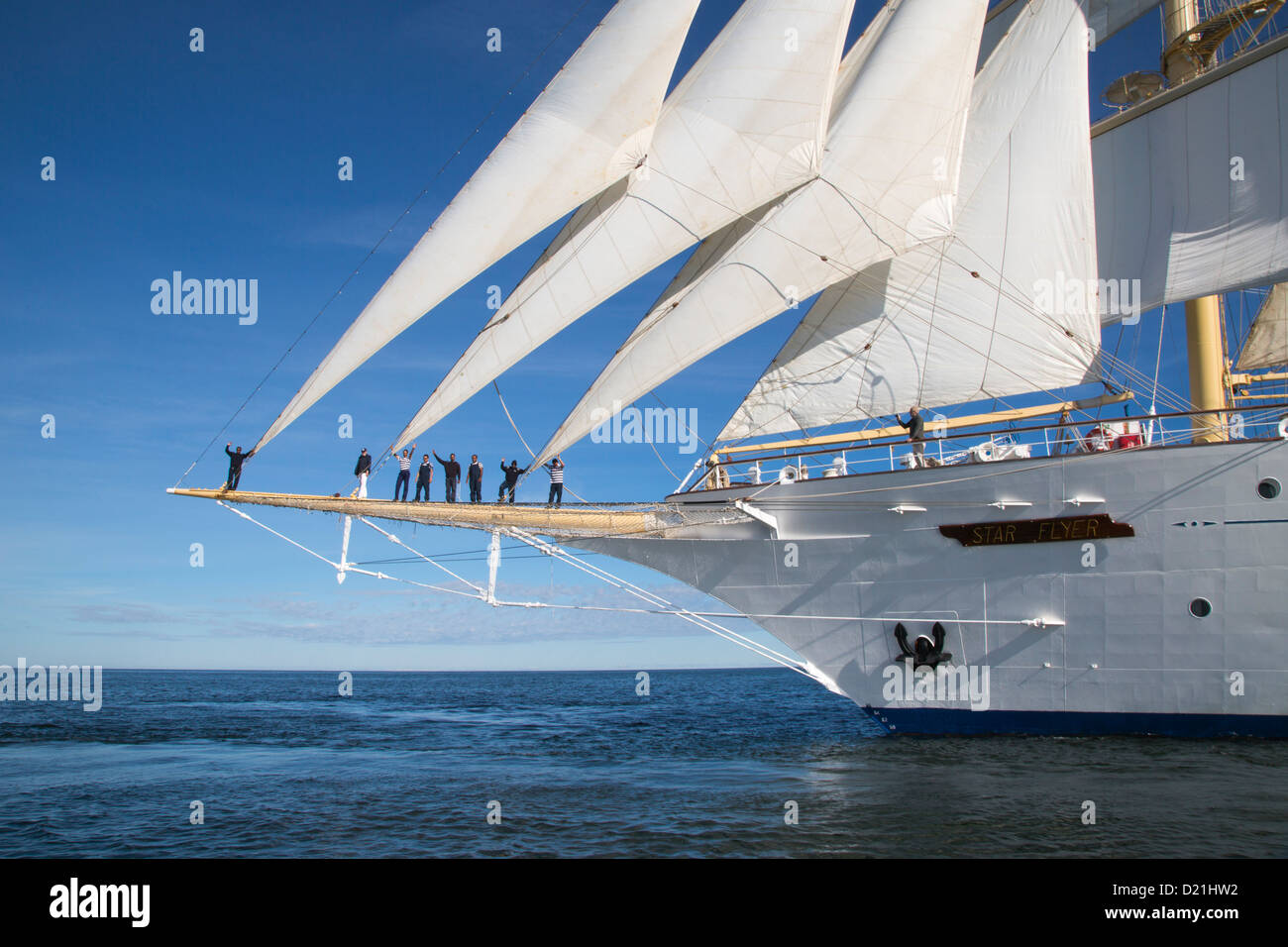 Captain Juergen Mueller-Cyran and sailors on bowsprit of sailing cruise ship Star Flyer under full sail, Baltic - Stock Image