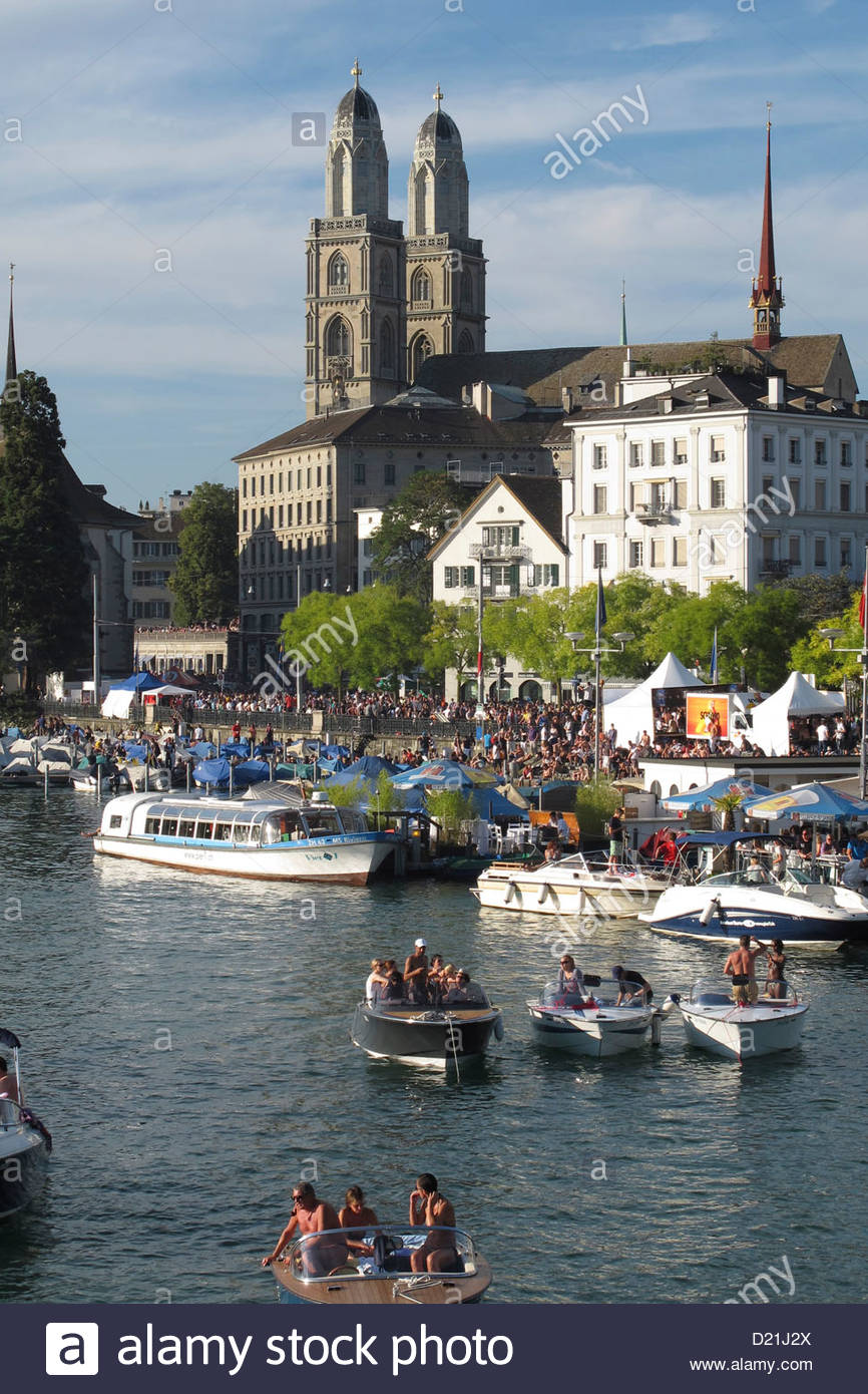 Boats at the Limmat River with the Great Minster in the background, Zurich, Switzerland - Stock Image