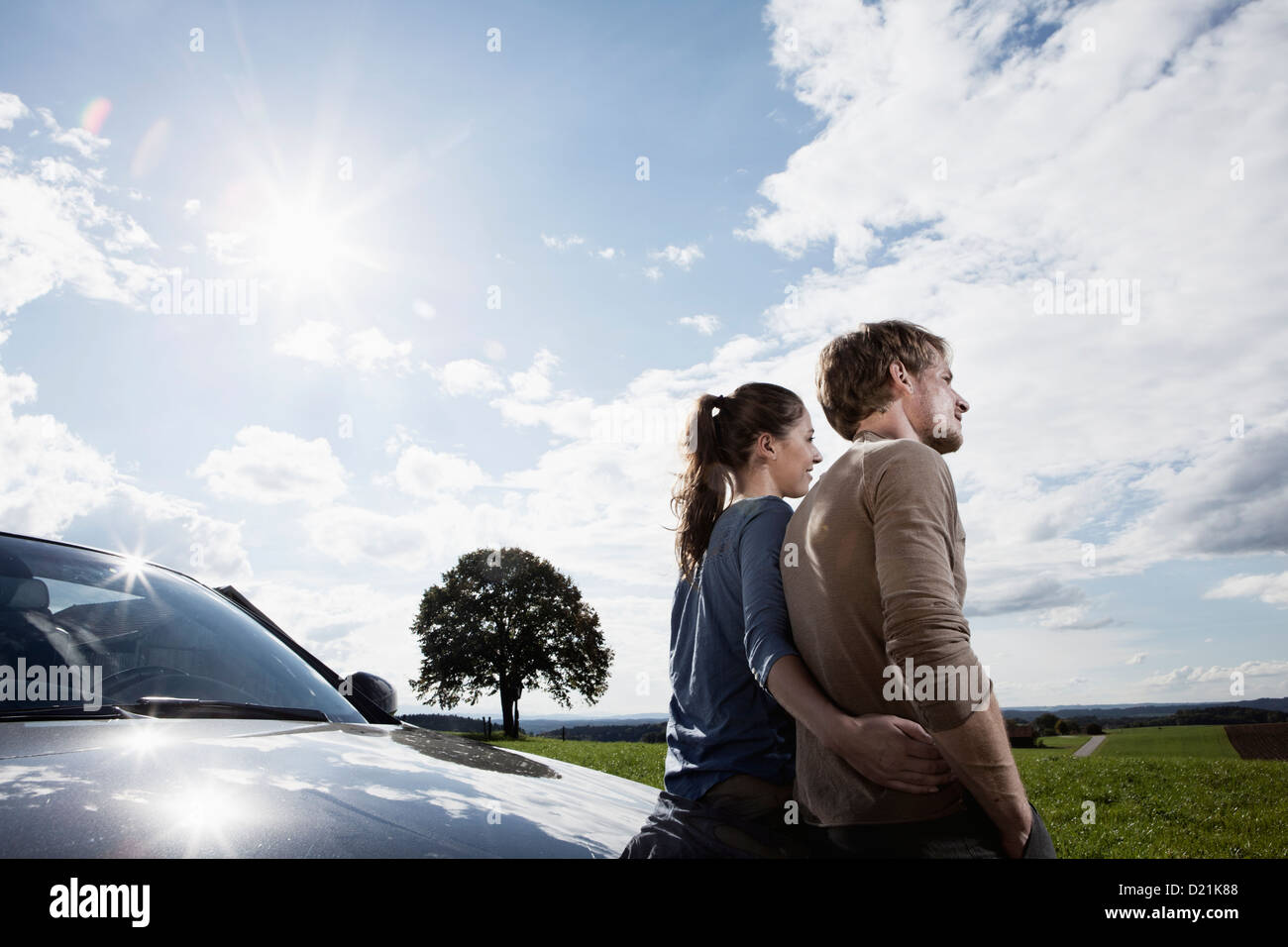 Germany, Bavaria, Couple standing by car - Stock Image