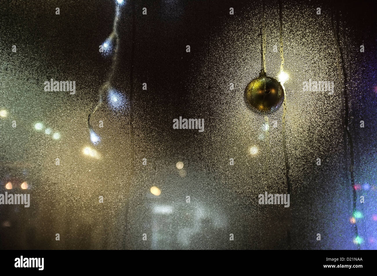 Condensation on a shop window, with bright lights glowing sparkling shining through, night, UK - Stock Image
