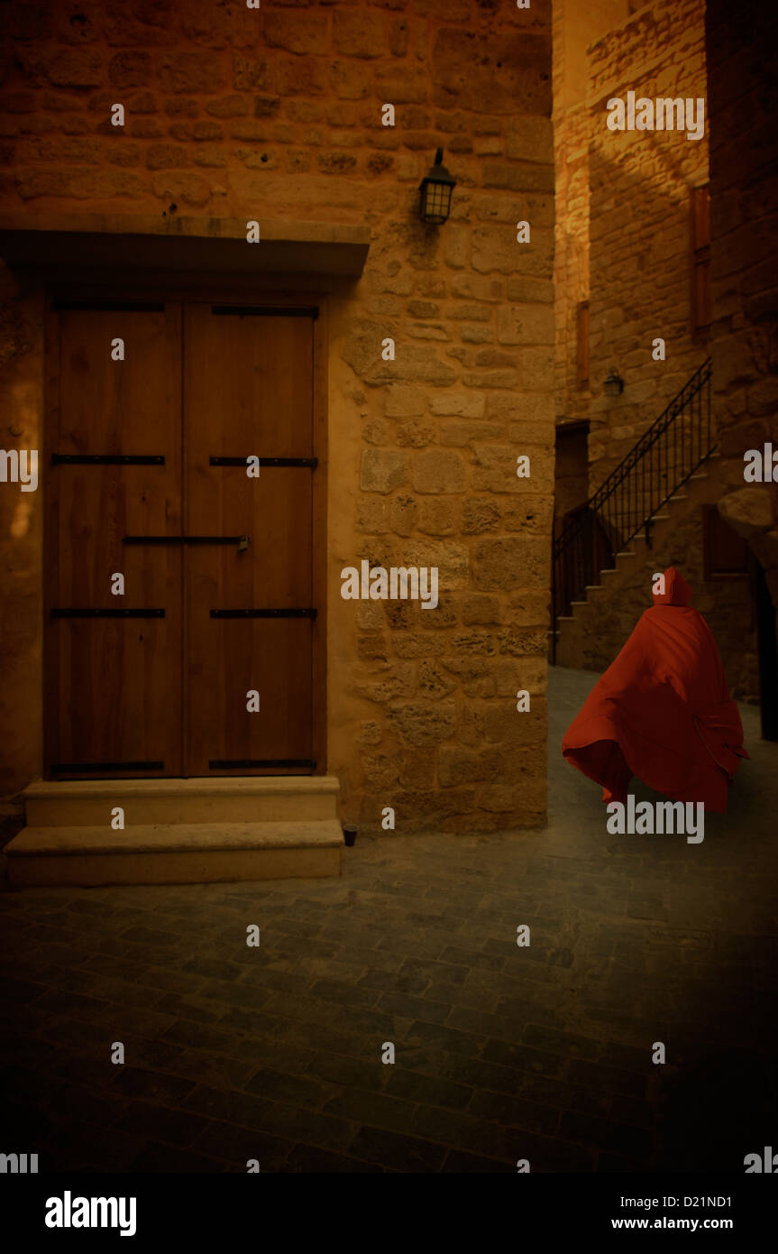 Mysterious figure in red cape running in the old village Stock Photo