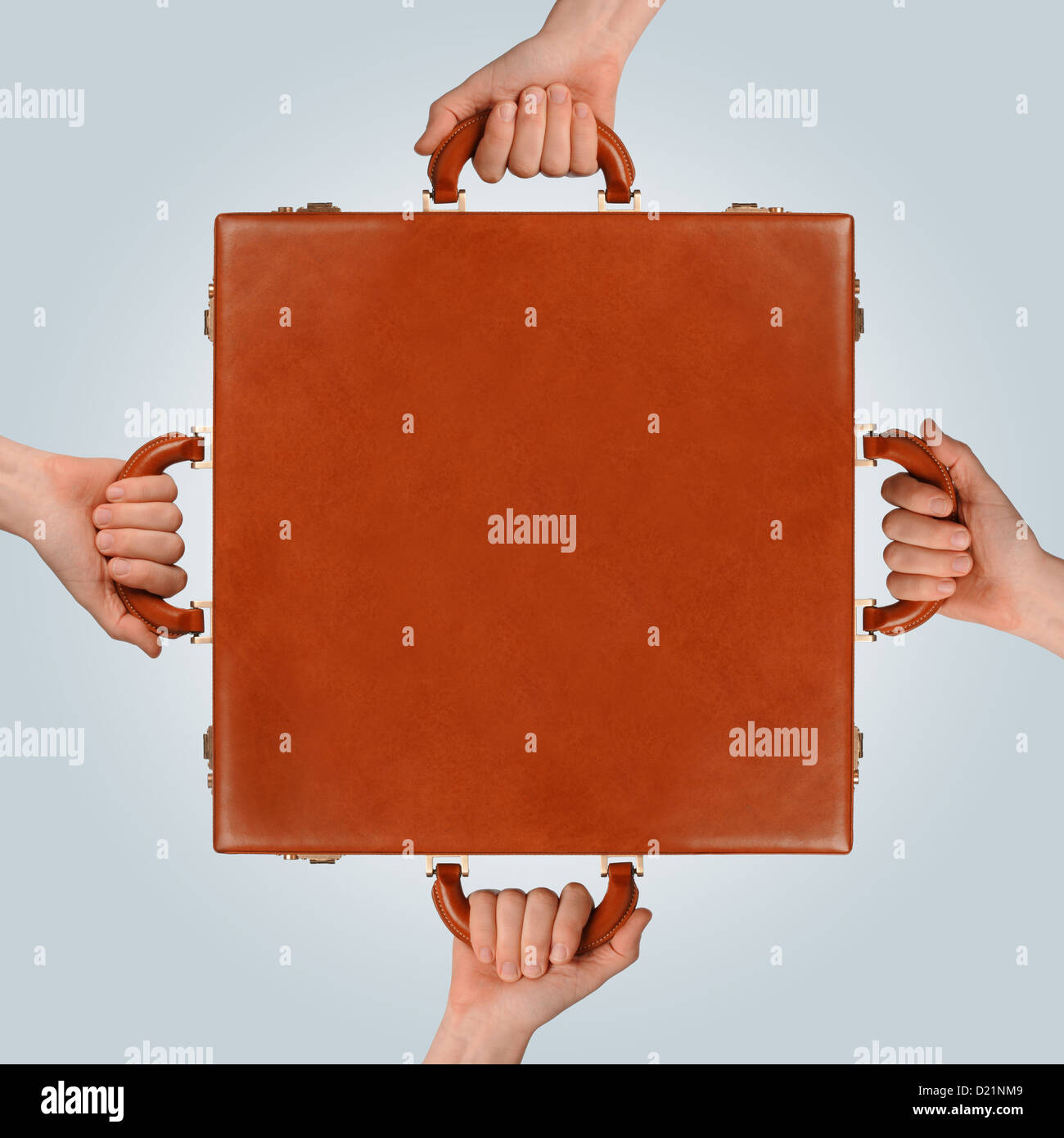 business teamwork concept showing multiple hands holding a briefcase - Stock Image