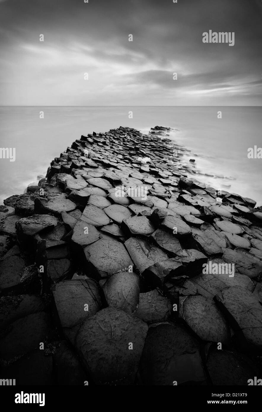 Black & white long exposure over the rocks and sea at the famous Giant's Causeway in Northern Ireland - Stock Image