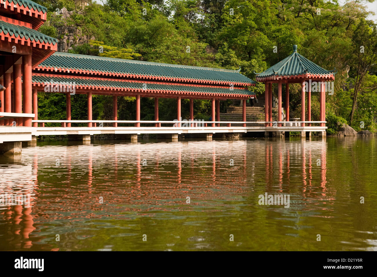 An ancient Chinese style bridge across the lake in Xishan Park in Guilin City in Guangxi Province in Southern China. Stock Photo