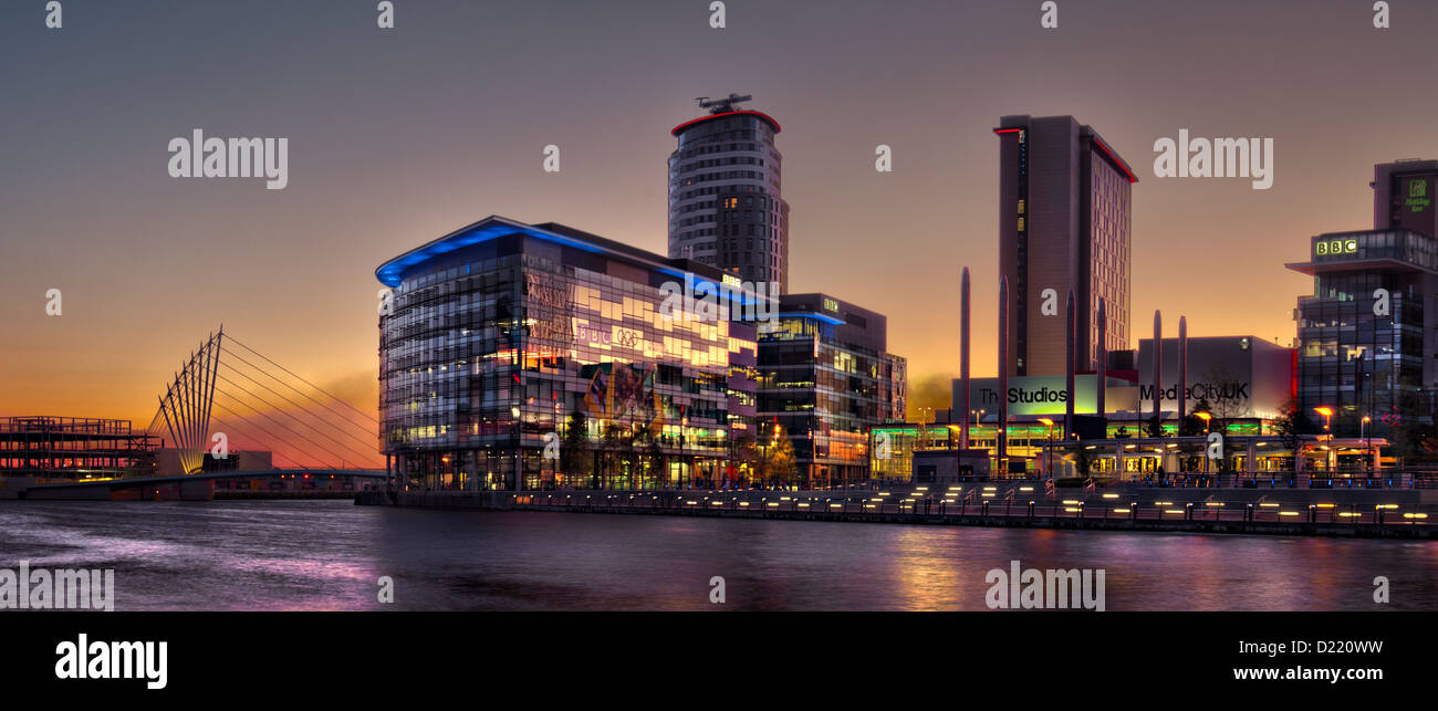Media City at Night. Panorama taken at sunset, with golden sky, lights on BBC Buildings, cable stayed swing bridge - Stock Image