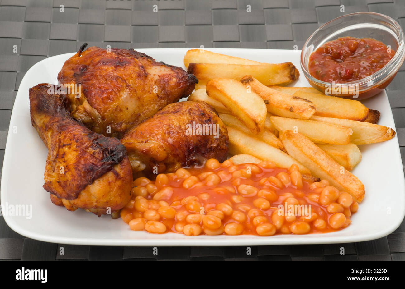 Barbecue chicken with French fries and baked beans - Stock Image