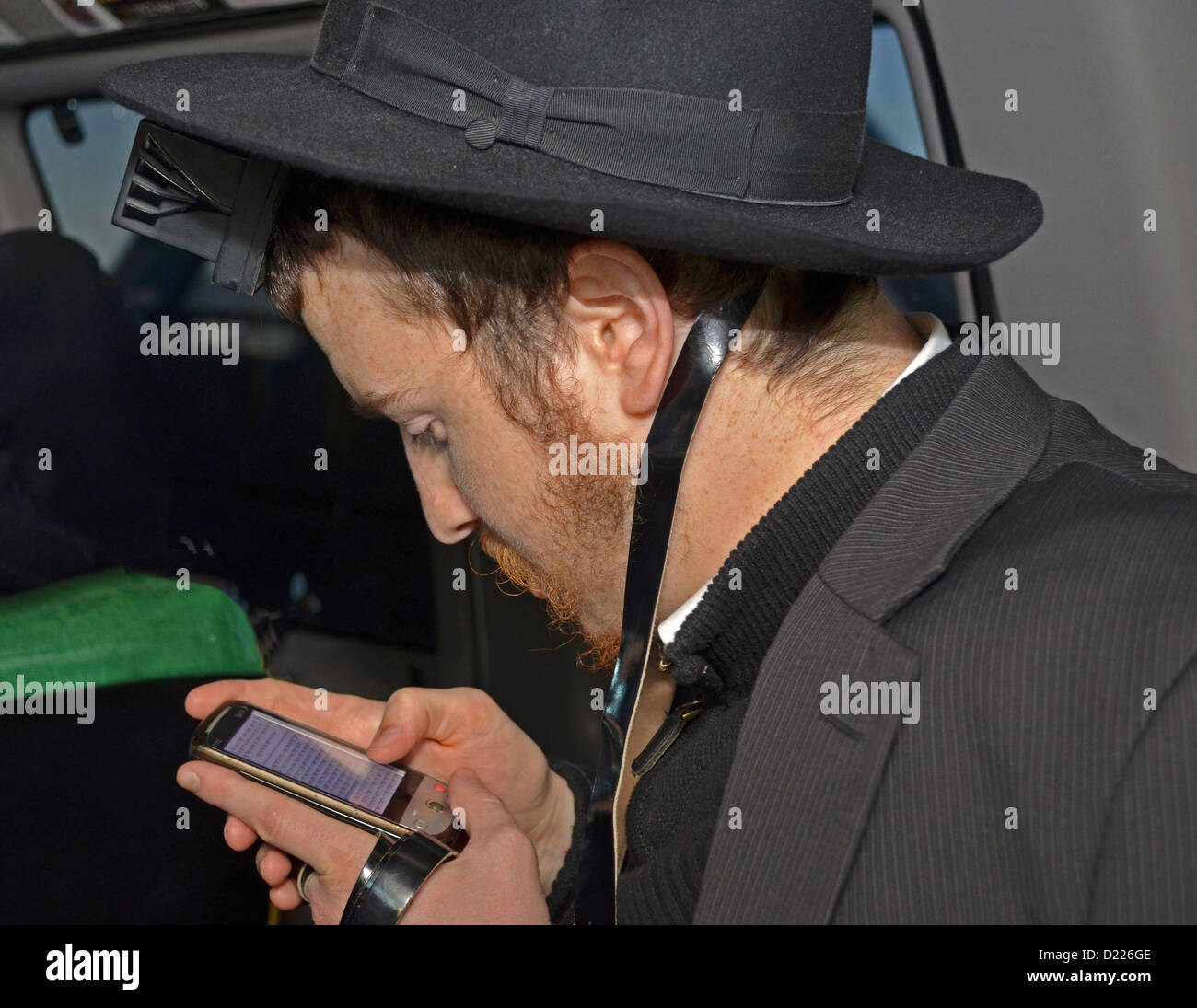 Orthodox Jewish student wearing phylacteries praying in a van while reading his prayers from a blackberry. - Stock Image
