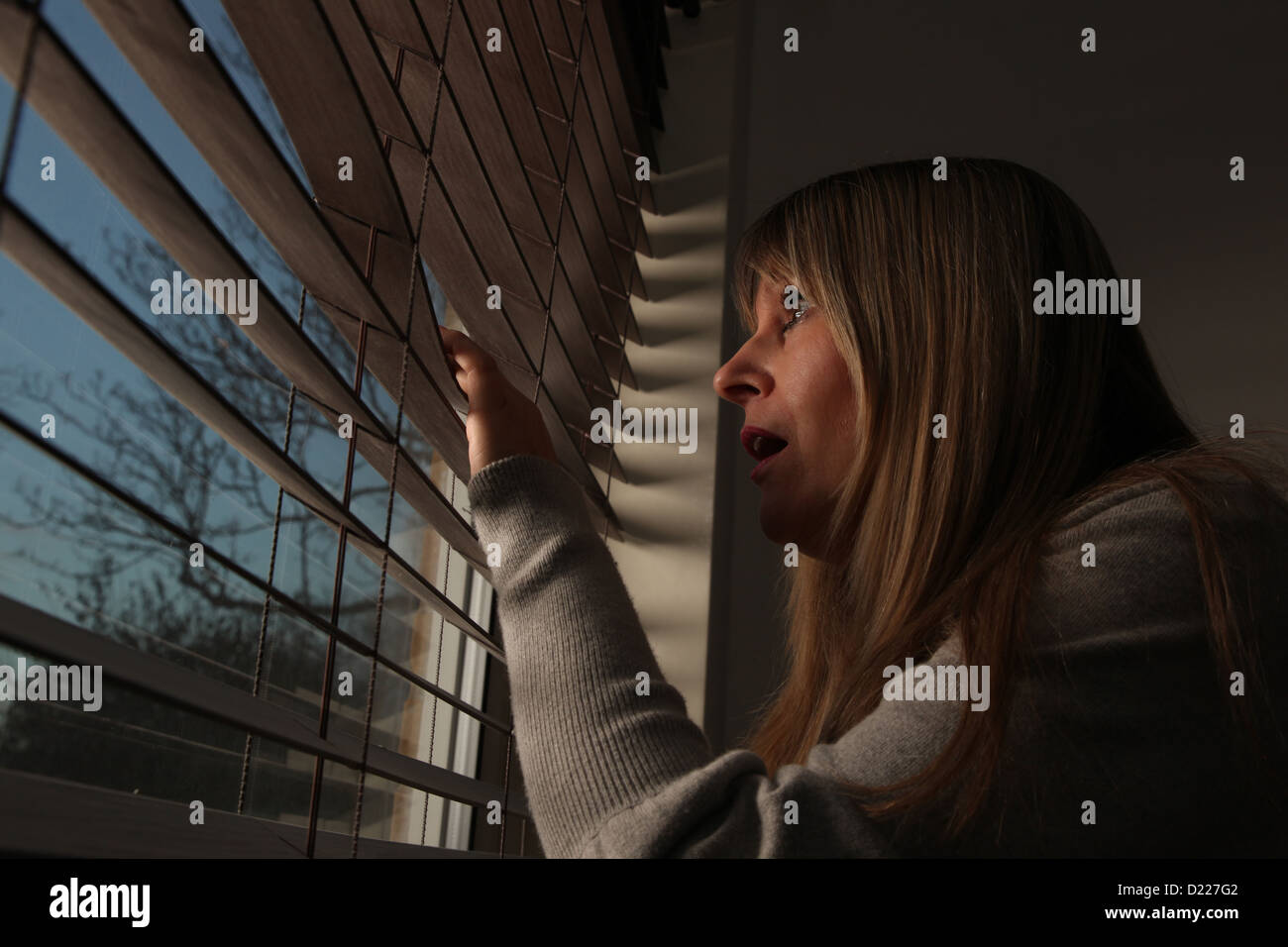 Anxious mature woman peering through window blinds at night. - Stock Image