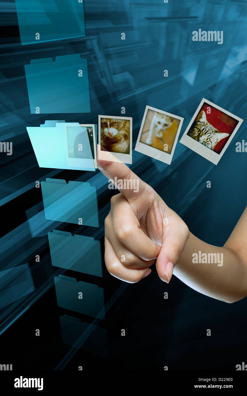 A woman finger open a folder, and data  on a digital screen - Stock Image