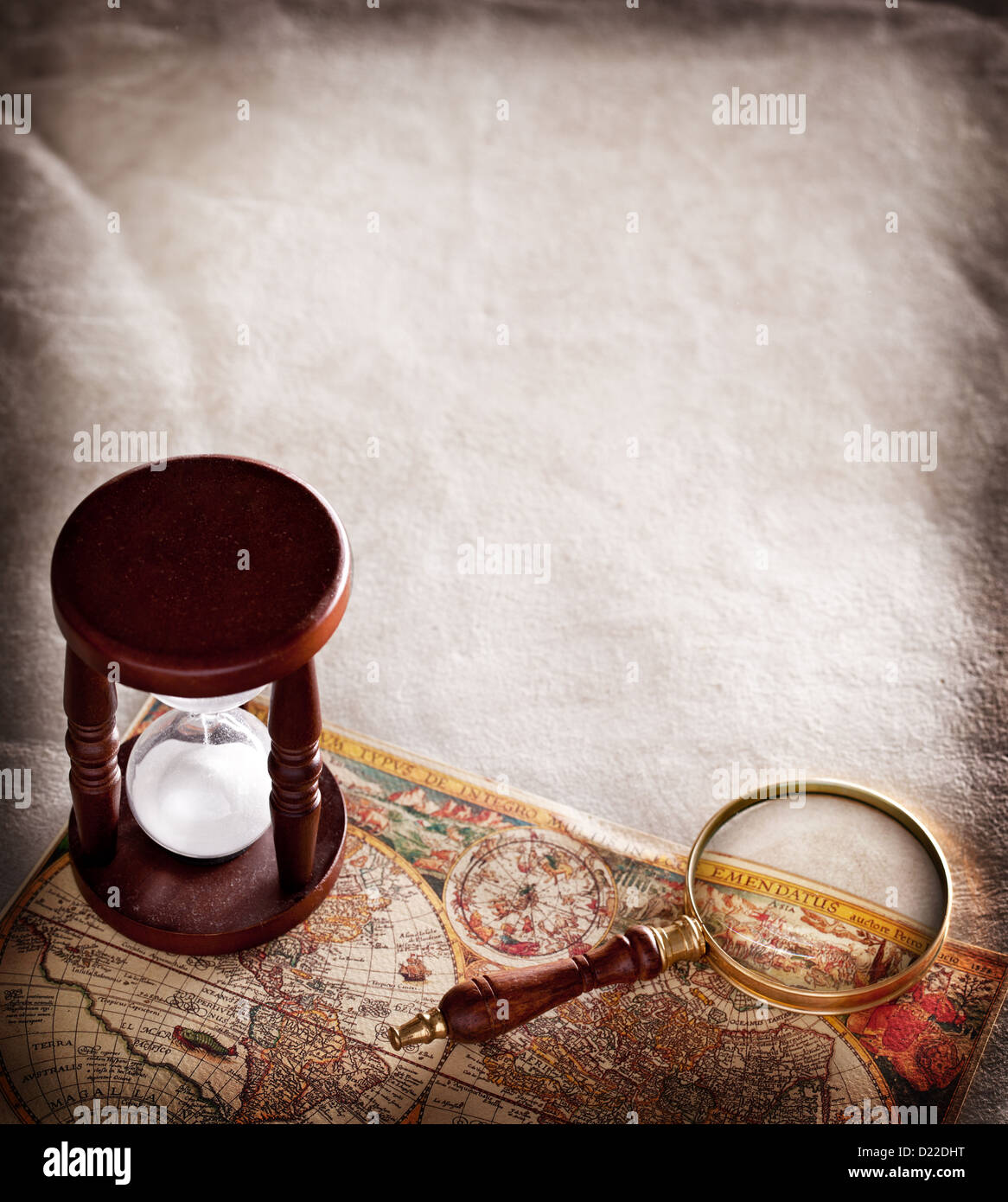 Hourglass with a magnifying glass on old parchment. - Stock Image