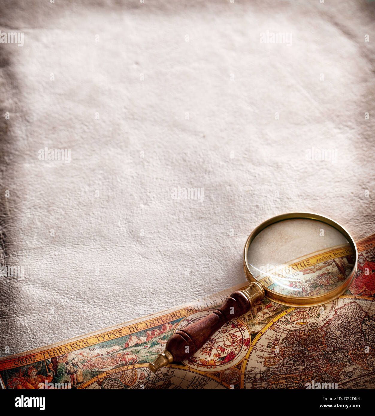 Magnifying glass on old parchment. - Stock Image
