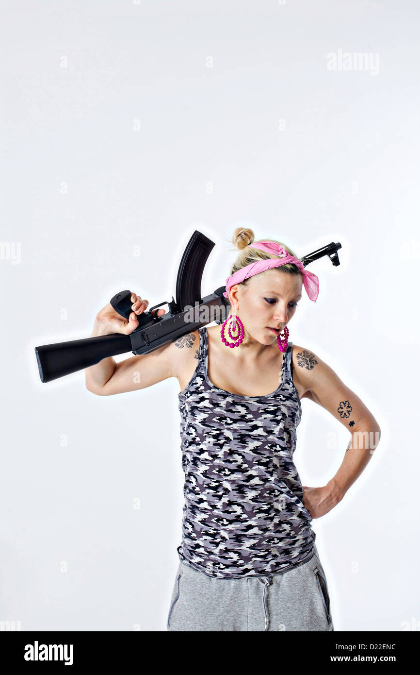 Dangerous young woman holding automatic rifle - Stock Image