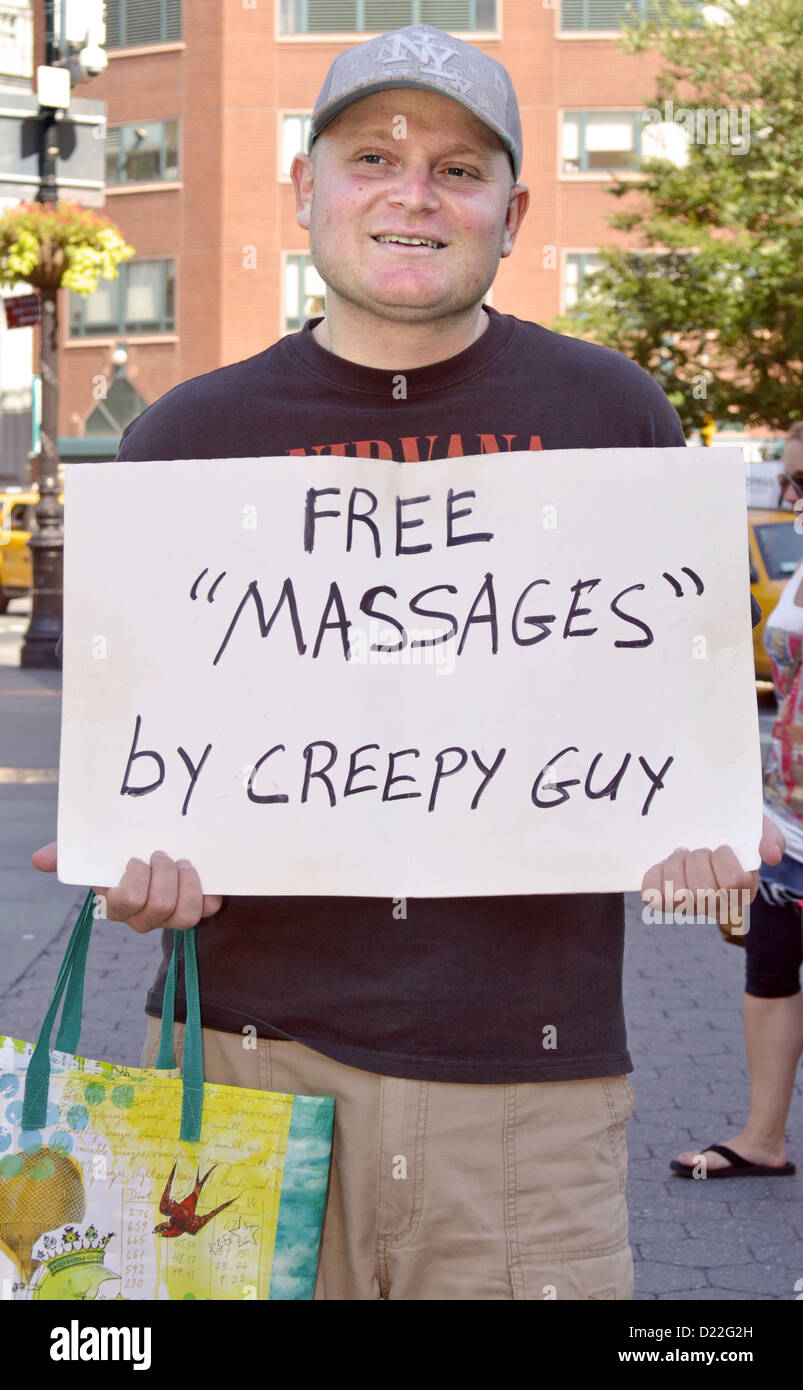 Portrait of a man in Union Square Park in Manhattan  holding sign 'Free Massages by Creepy Guy' - Stock Image