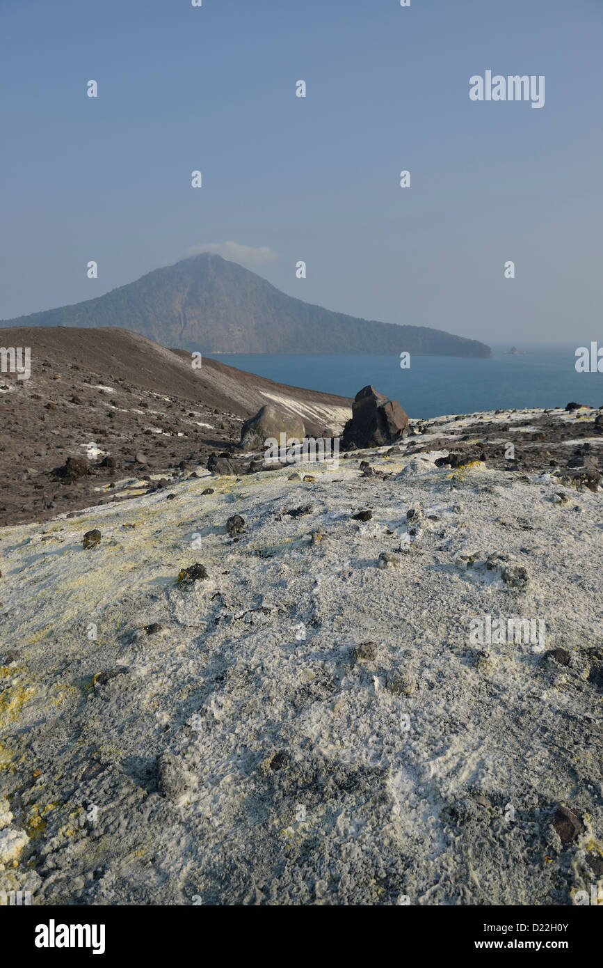 The sulphur covered slope of Anak Krakatau with the island of Rakata in the background; Western Java, Indonesia. - Stock Image