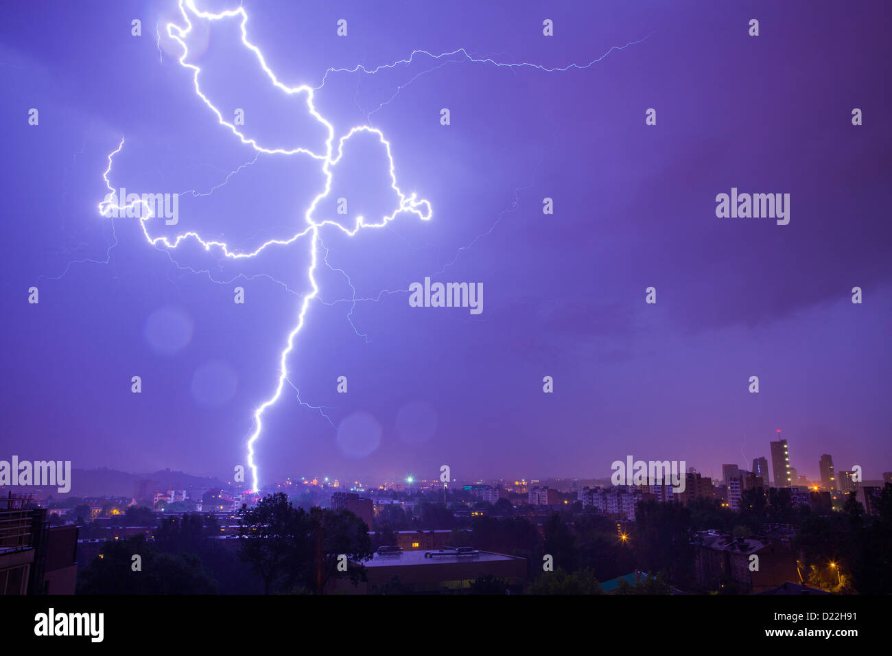 Lightning hits the city on a rainy night - Stock Image