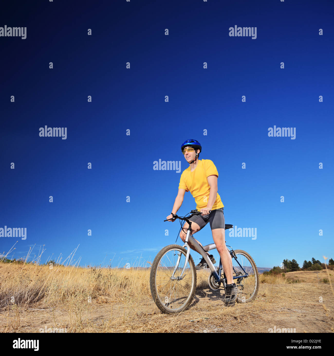Panning shot of a bicycle rider riding a mountain bike outdoors on a sunny day against a cloudless blue sky - Stock Image
