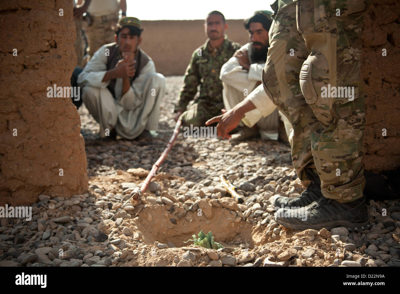 A coalition forces member (right) watches Afghan National Security Forces analyze a notional danger area during - Stock Image