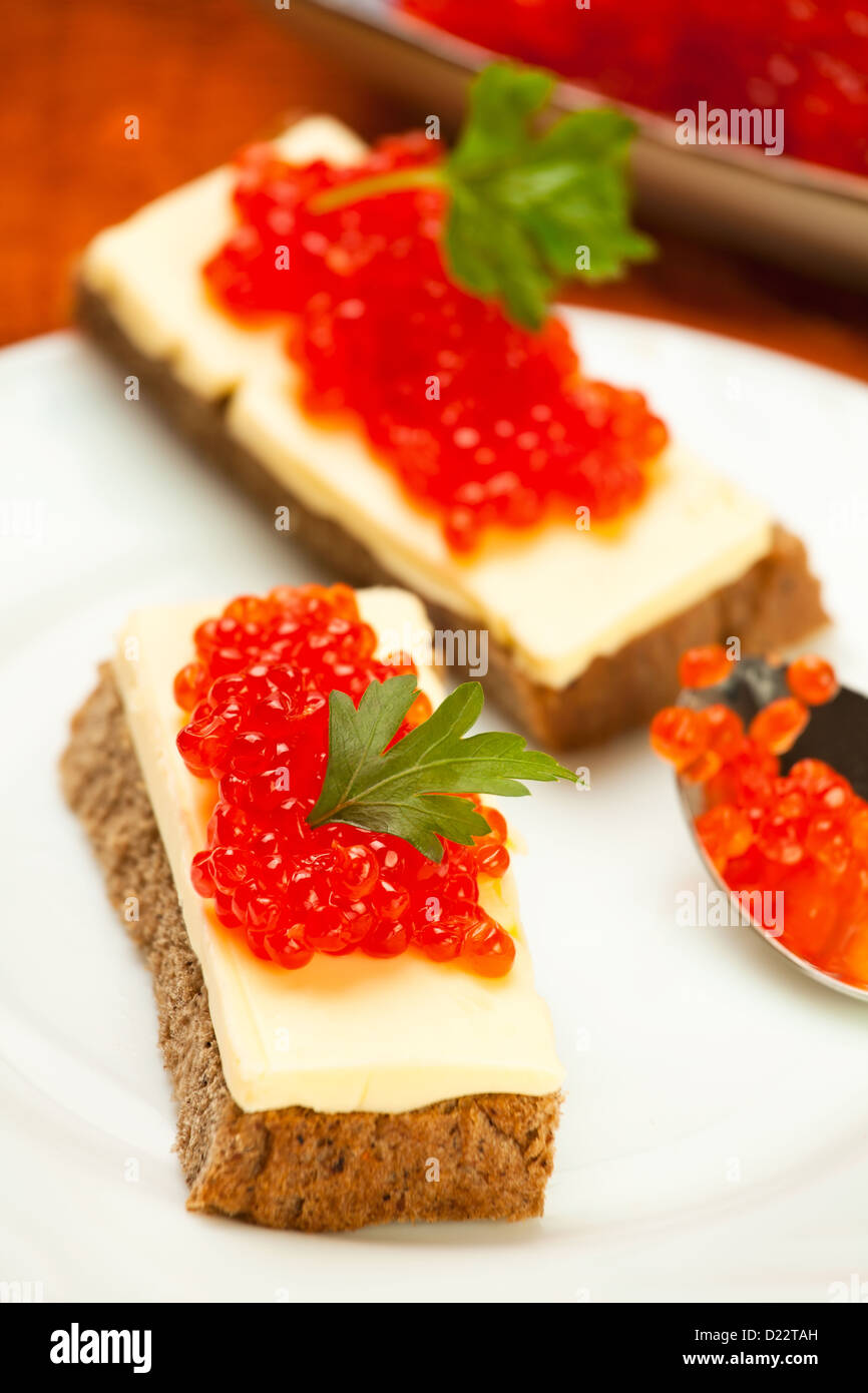 caviar red sandwich on white plate - Stock Image