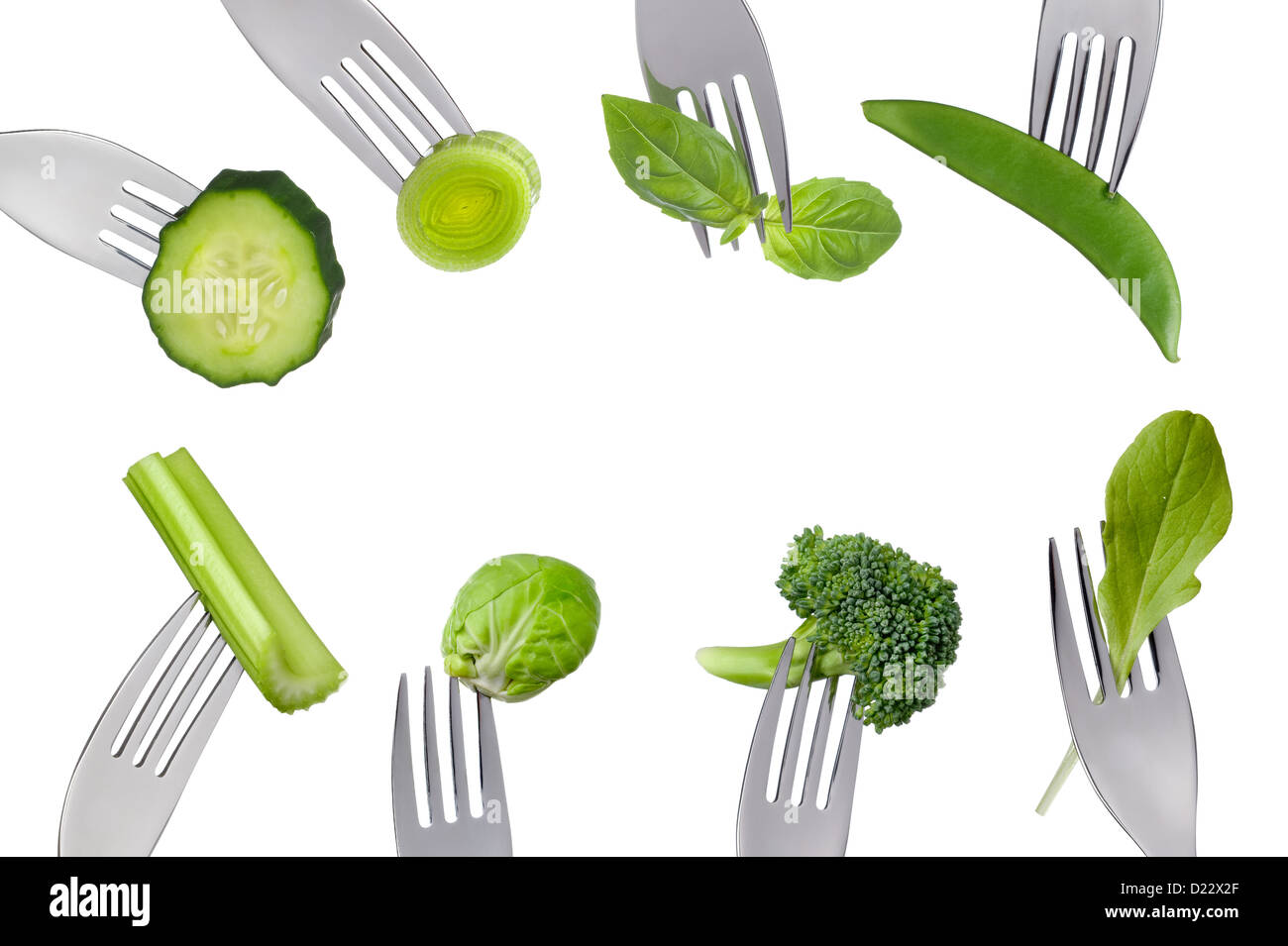 fresh green healthy vegetables on forks isolated against white background forming a border with copy space - Stock Image