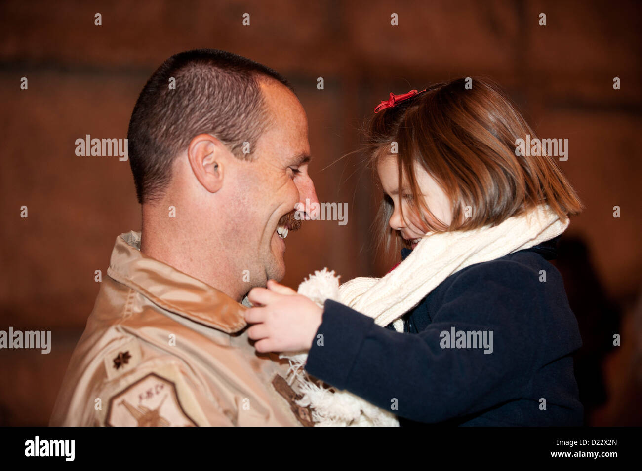 U.S. Air Force Major Mike Gommel, 120th Fighter Squadron, smiles at his daughter after returning home at Buckley Stock Photo