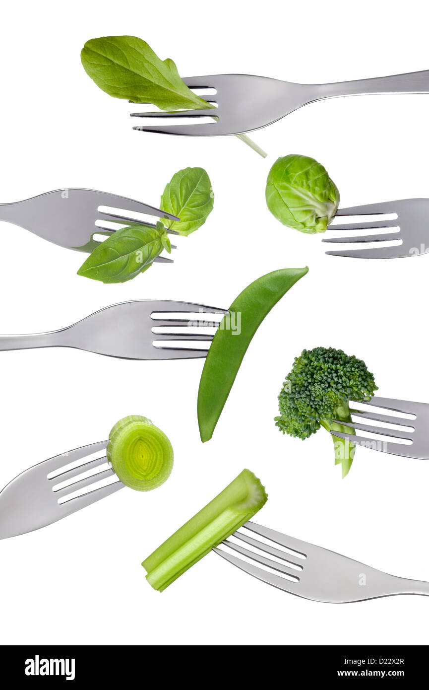 variety of fresh green healthy vegetables on forks isolated against a white background - Stock Image