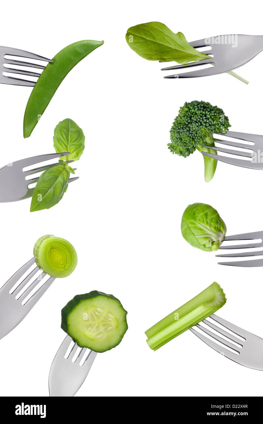 border of fresh green vegetables on forks isolated against white background. Healthy food concept - Stock Image