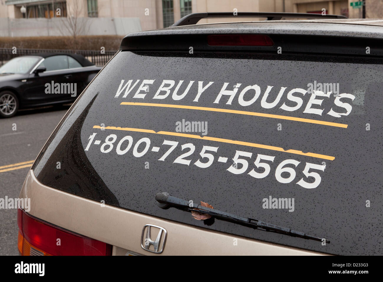 We Buy Houses ad on rear windshield - Stock Image