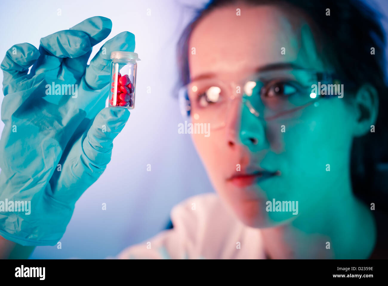 Laboratory assistant holds a bottle of pills in her hand - Stock Image