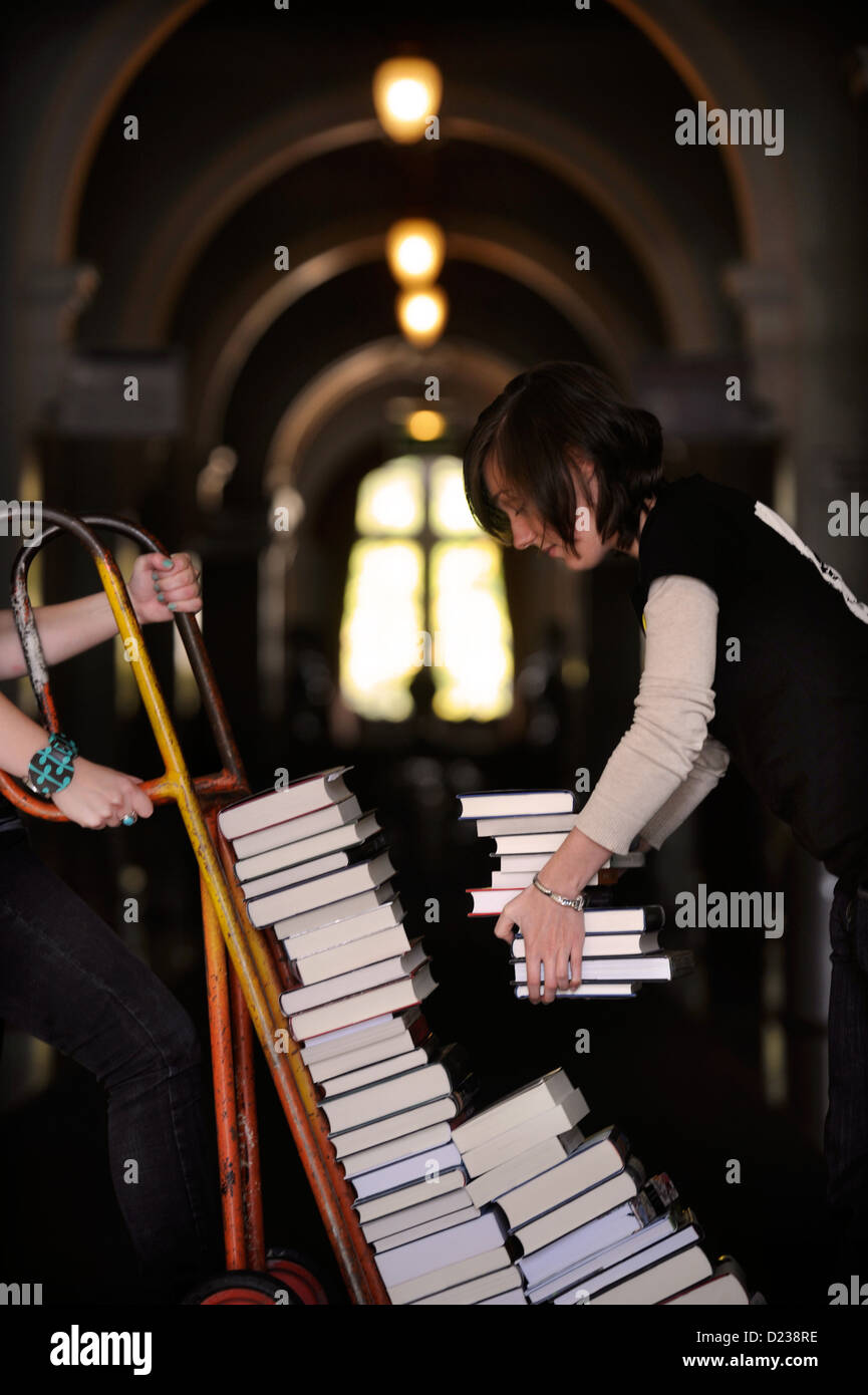 Festival organisers manouver a stack of books on a sack truck at the Cheltenham Literature Festival UK - Stock Image