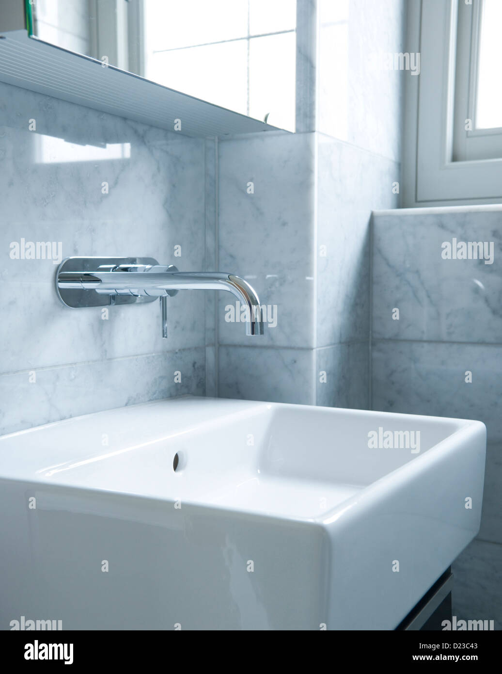 A bathroom sink with chrome tap and tiled walls Stock Photo ...