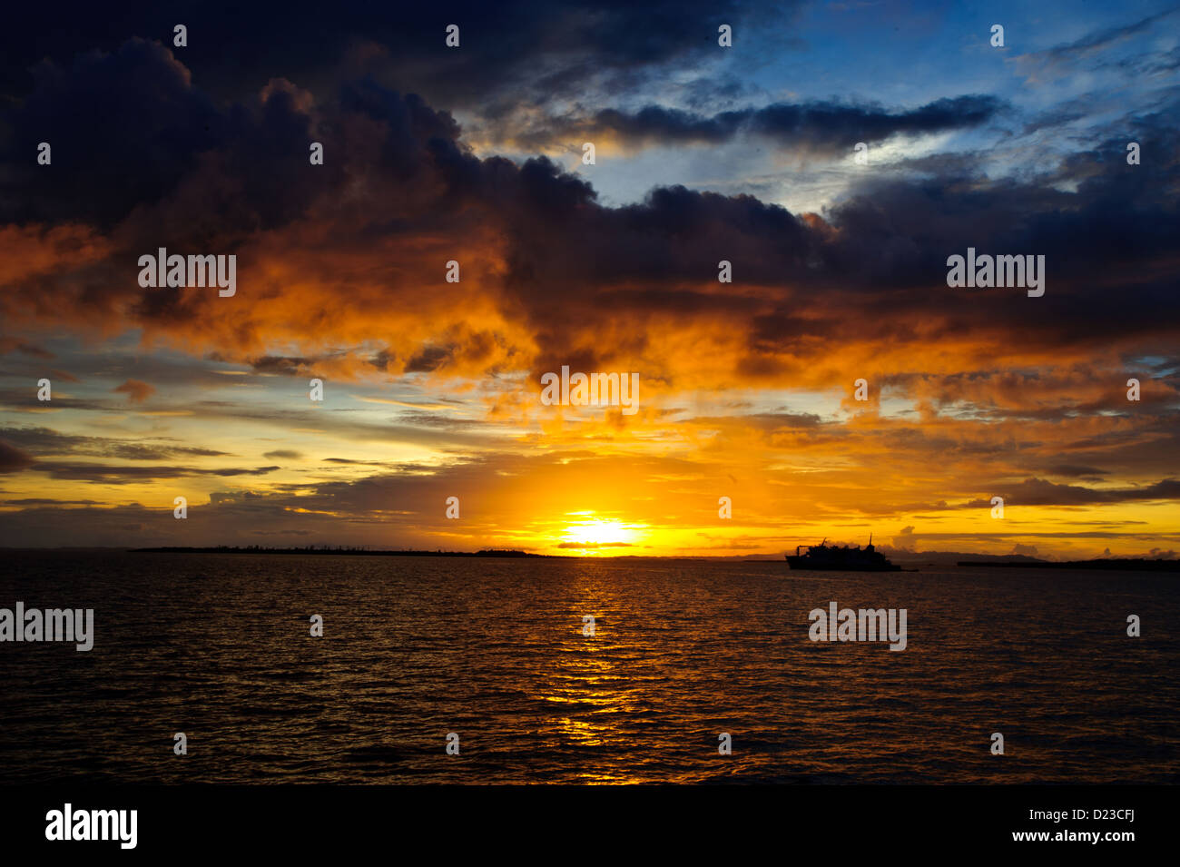The sun setting on the flat calm ocean in Sorong Raja Ampat West Papua. Boat and Island silhouette, warm light. - Stock Image