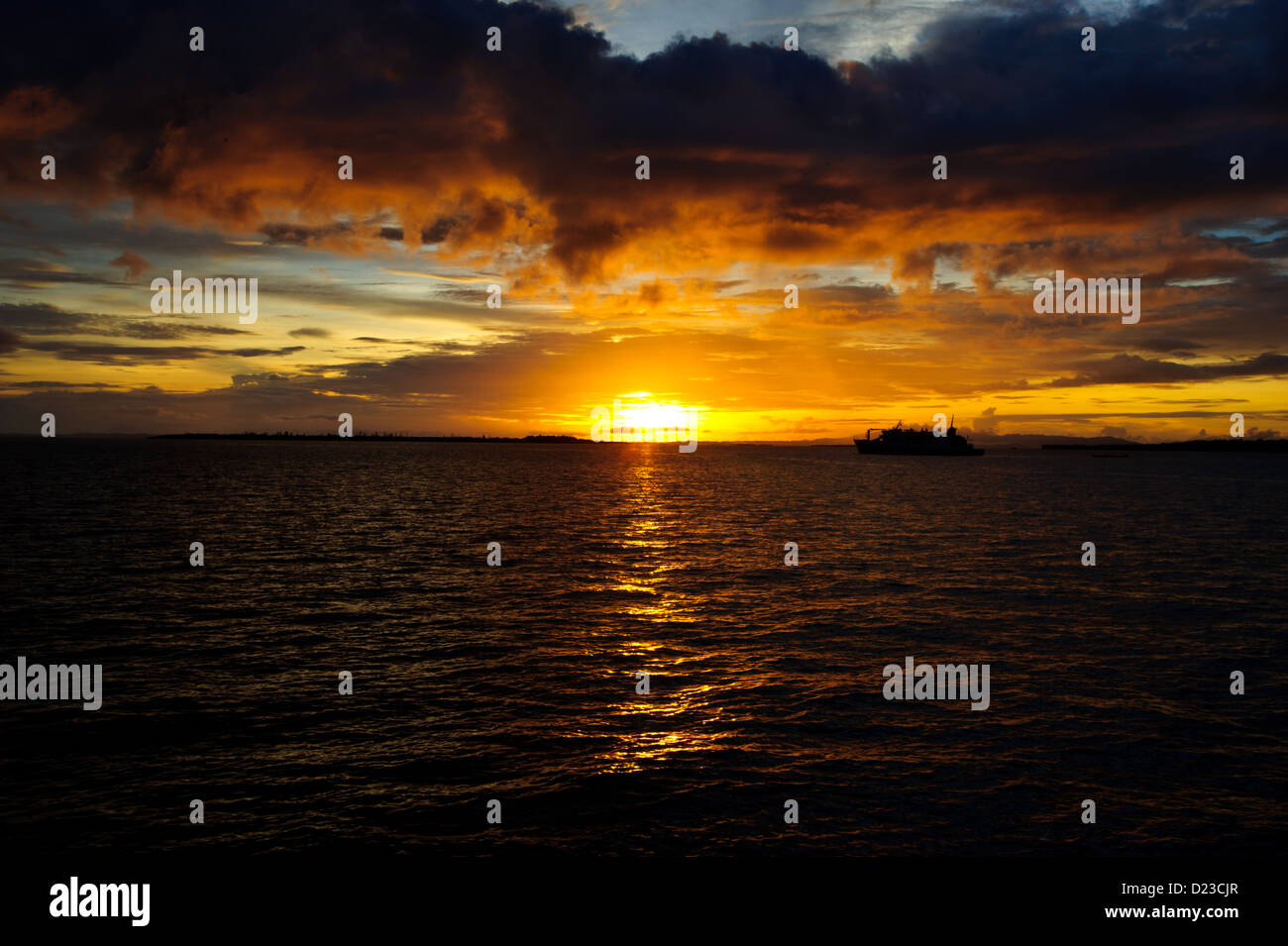 The sun setting on the flat calm ocean in Sorong Raja Ampat West Papua. Dark ocean below dark clouds above warm Stock Photo