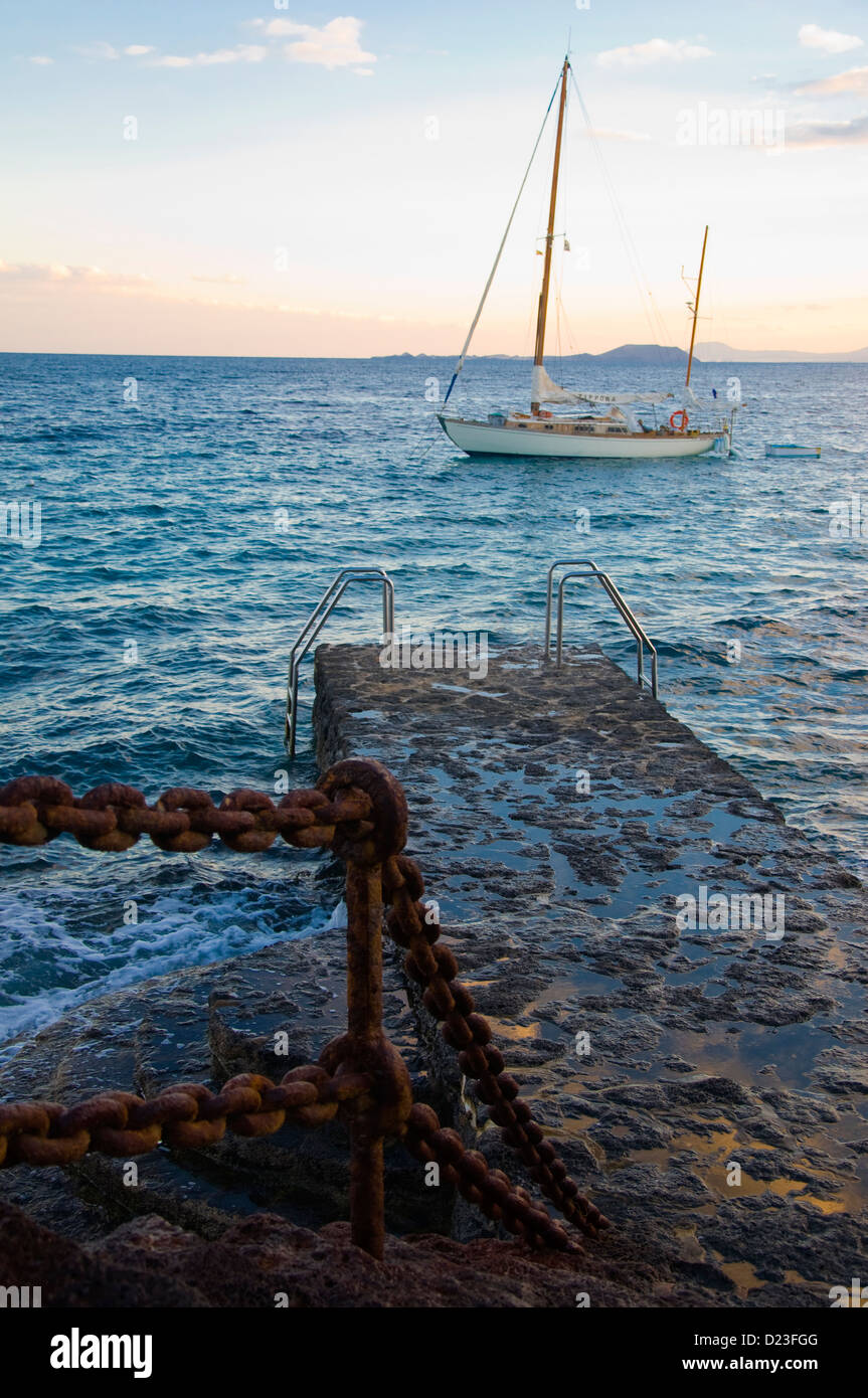 Sail boat and pier, Playa Blanca, Lanzarote, Spain - Stock Image