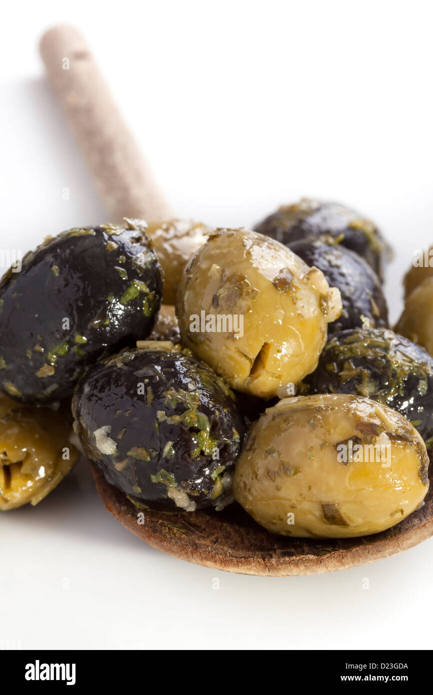 Green and black olives on wooden spoon - Stock Image