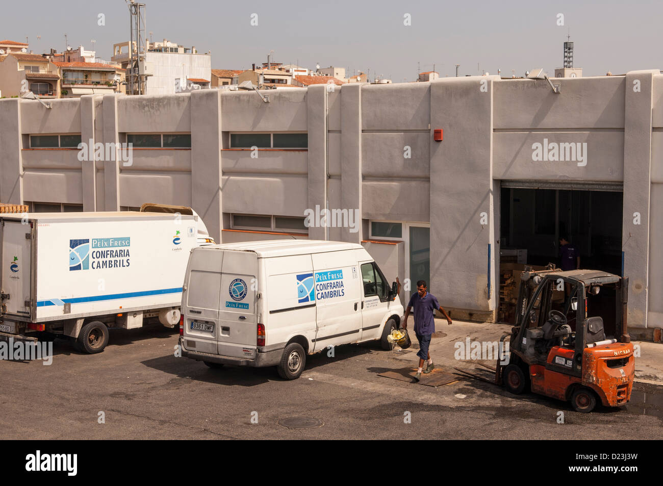 Men at work in the fishing industry in the fishing port of Cambrils , Costa Dorada , Spain - Stock Image