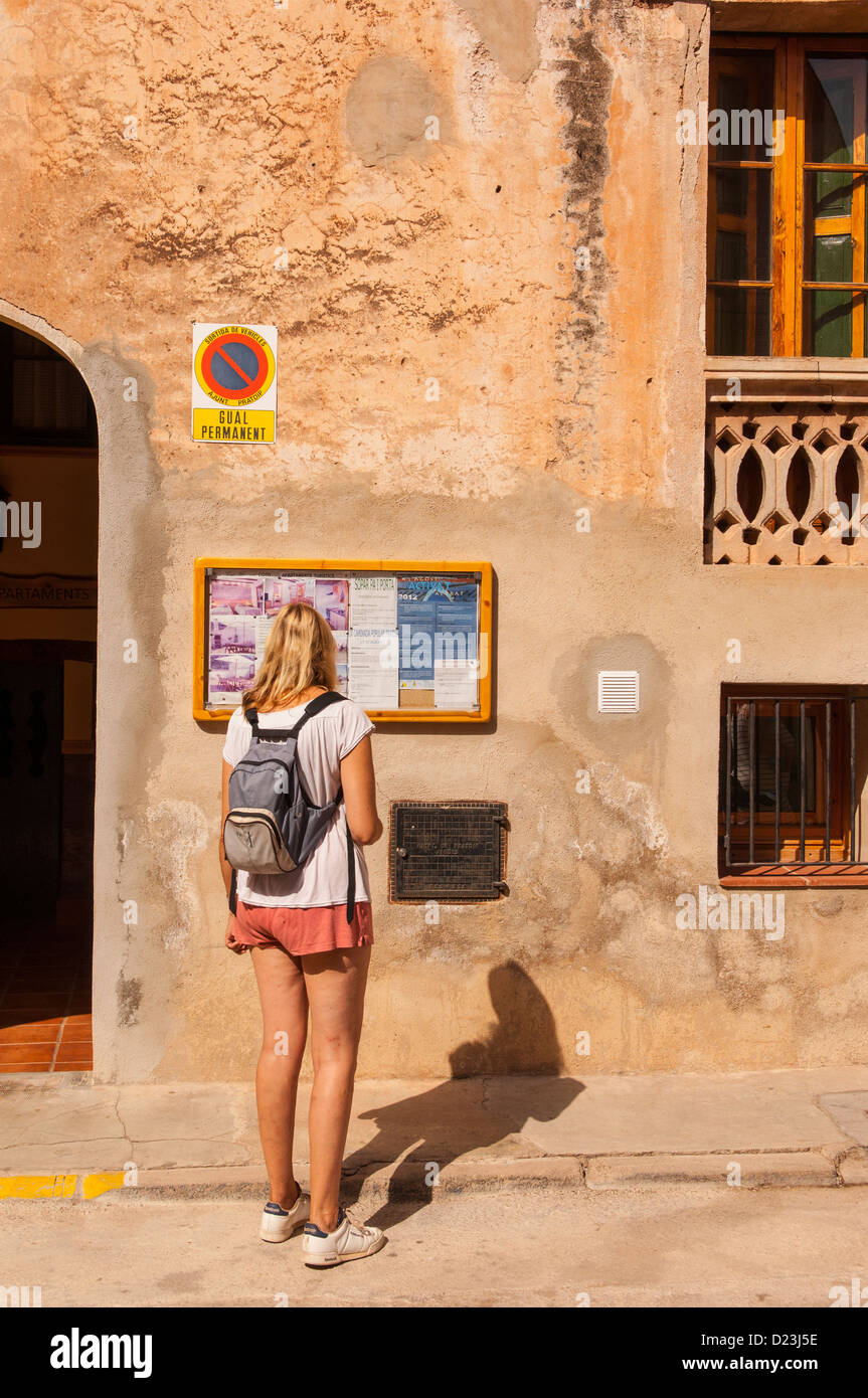 A woman reading a notice board in the old village of Pratdip , Costa Dorada , Spain - Stock Image