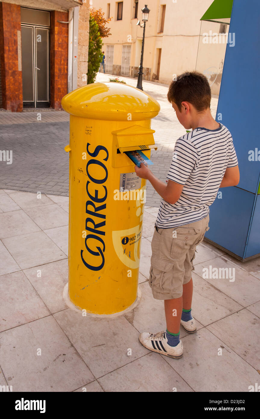 A 12 year old boy posting postcards in a postbox in Spain - Stock Image