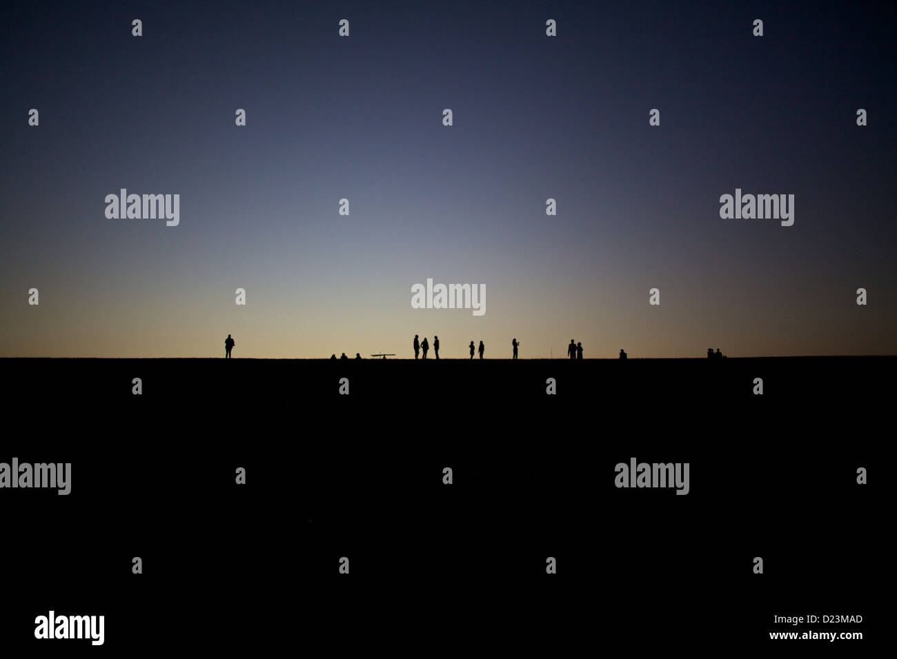 A crowd gathers on top of a levee in Bywater to watch the sunset over New Orleans - Stock Image