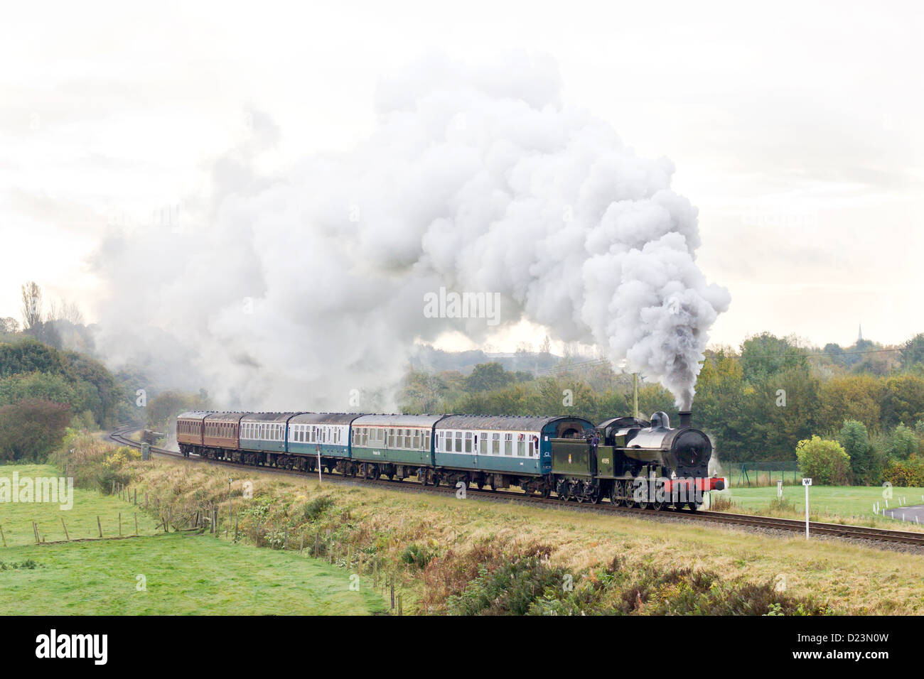 Steam locomotive pulling a passenger train on the East Lancs Railway at Burrs - Stock Image