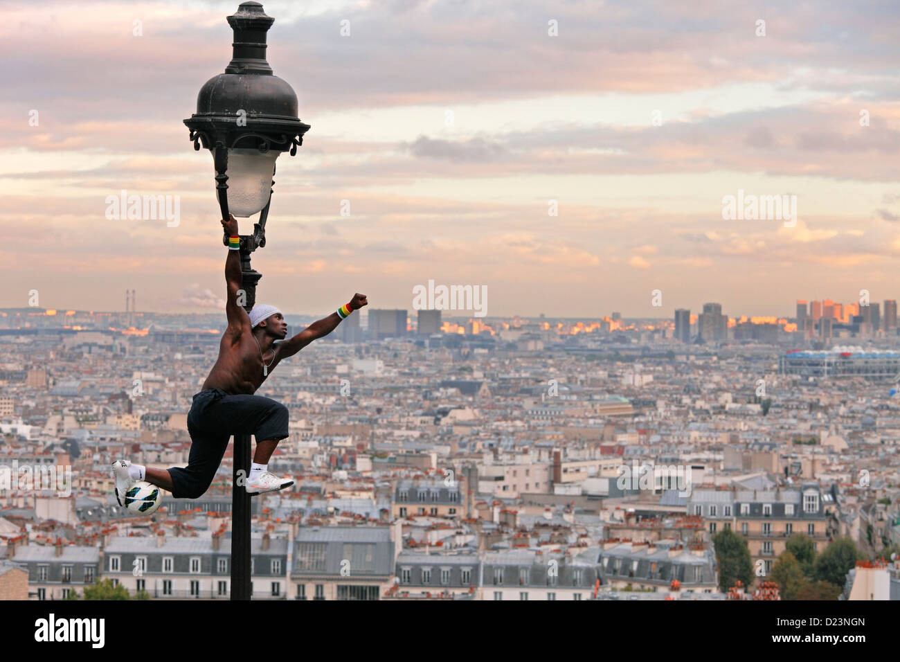 acrobatic performance artist at an old gas lamp on the hill of Sacre Coeur and view of Montmartre and Paris - Stock Image
