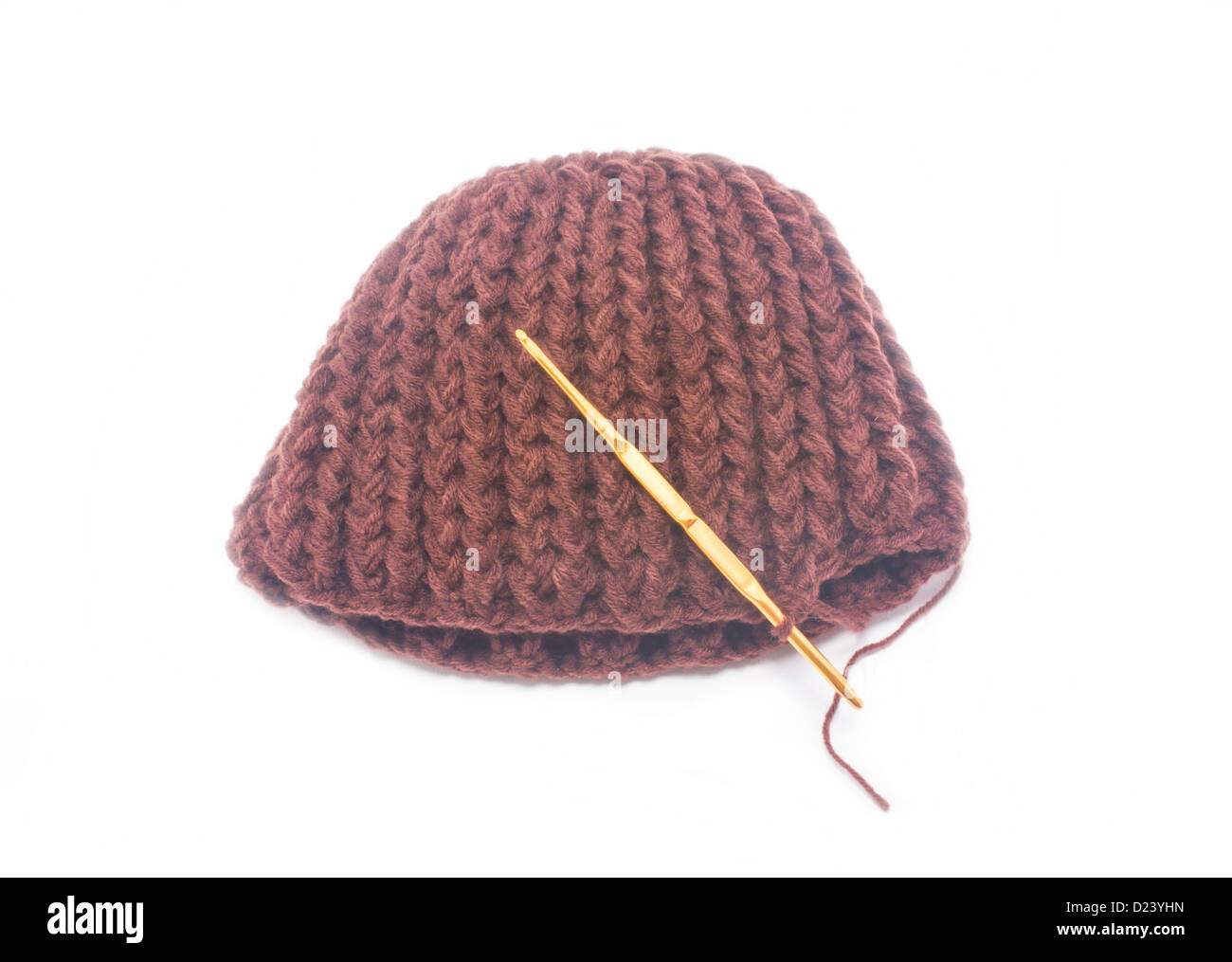 f61f8882 Brown crochet hat with golden hook isolated on white background ...