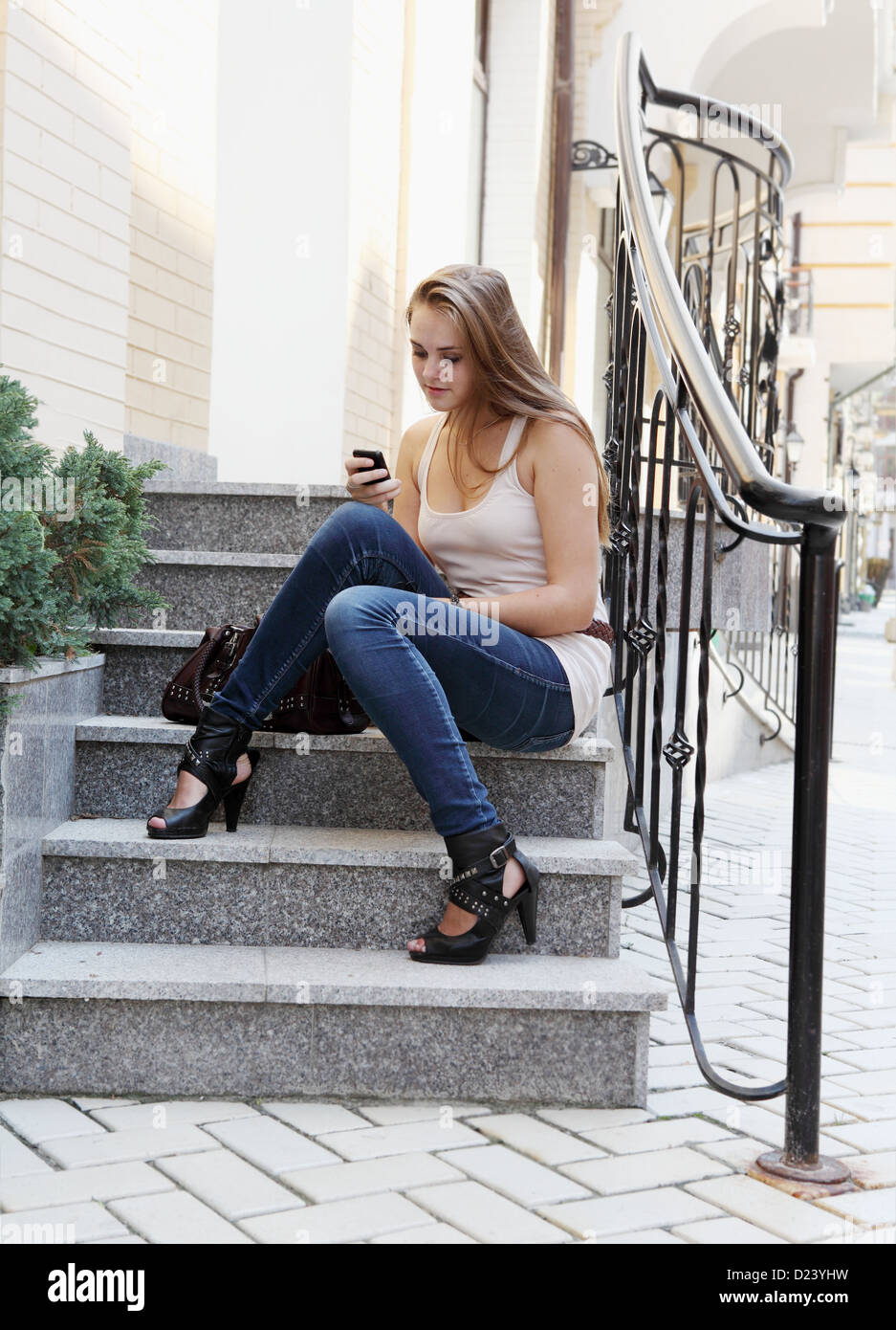 Young Woman Calling by Phone Outdoors Urban Scene Stock Photo