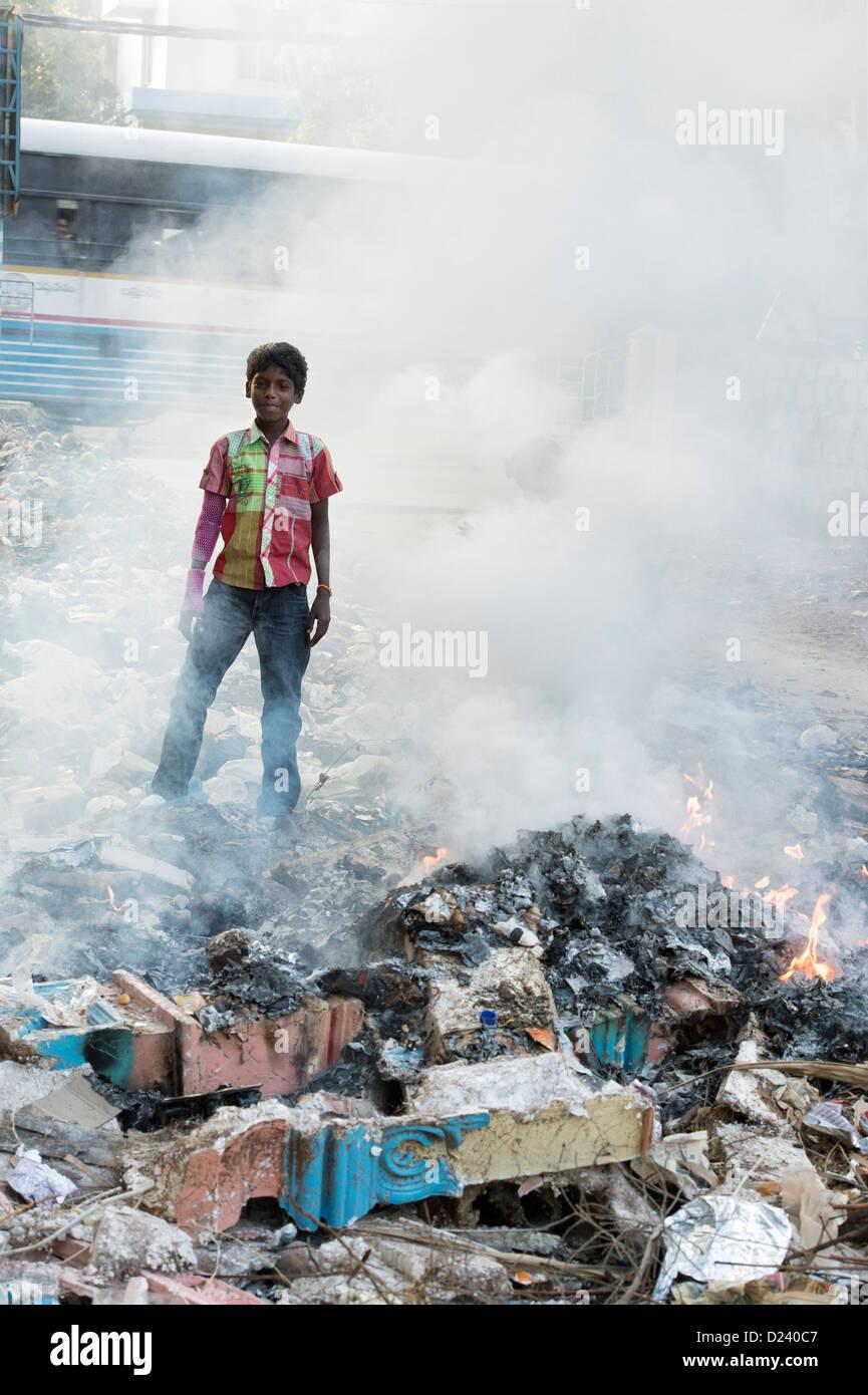 Indian boy standing in amongst burning household waste. Andhra Pradesh, India - Stock Image