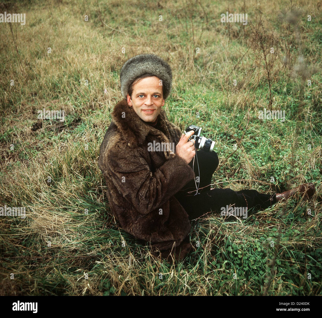 (dpa files) - German actor Klaus Kinski sits in the grass, holding a camera, 2 September 1969. An 'enfant terrible' of the film industry, his films include 'Aguirre, der Zorn Gottes' ('Aguirre: The Wrath of God') and 'Nosferatu: Phantom der Nacht' ('Nosferatu the Vampire'). Kinski was born on 18 October 1926 in Zoppot/Danzig, Germany (now Sopot/Gdansk, Poland) under the name of Nikolaus Guenther Nakszynski and died on 23 November 1991 in Lagunitas, California, of a heart attack. Stock Photo