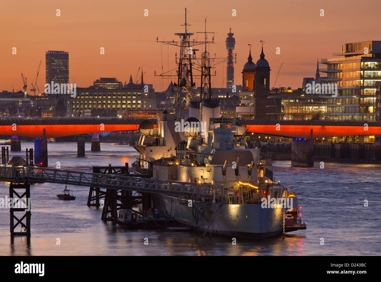 HMS Belfast moored on the Thames with London bridge skyline and post office tower in background at sunset, London, - Stock Image